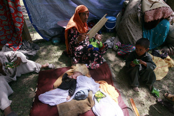 An Internally displaced woman, fleeing military operations in Swat, sits with her children in a roadside shelter in Takht Bai