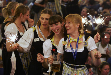 Waitresses dance on tables with sparklers while celebrating the end of Munich's Oktoberfest