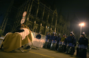 A woman on a wheelchair waits for ambulance on street in front of parliament building in Budapest