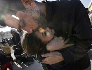 Prisoner embraces his daughter during family visit at Iraqi military prison in Baghdad
