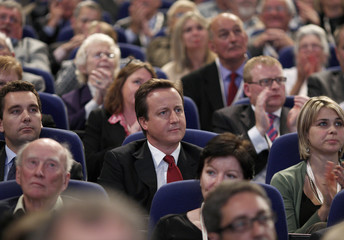 Britain's Conservative Party leader David Cameron listens to London Mayor Boris Johnson speak during the Conservative Party annual conference in Birmingham, central England