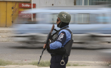 An Iraqi policeman directs traffic in Baghdad