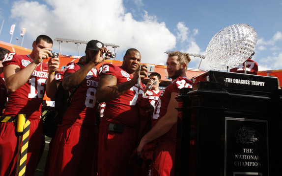 University of Oklahoma players take pictures of the national championship trophy during media day at the Dolphins stadium in Miami