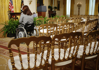 A woman in a wheelchair waits for the start of an event for the signing of a proclamation celebrating the 19th anniversary of the Americans with Disabilities Act in the East Room at the White House in Washington