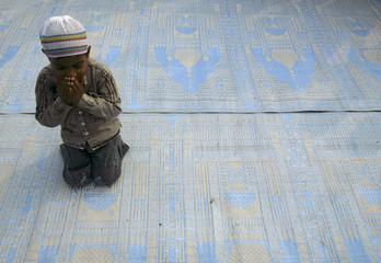 boy offers Eid al-Adha prayers in the northeastern Indian city of Siliguri