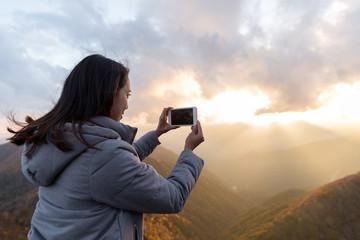 Woman taking photo on cellphone at Mount Hangetsuyama during sunset