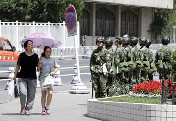 Women walk next to policemen as they stand guard at the main square of Urumqi in Xinjiang Autonomous Region