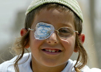 A Jewish boy with a patch featuring the Israeli flag smiles on the beach near the settlement of Neve..