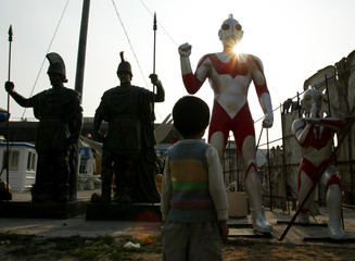 CHILD LOOKS AT AN ULTRAMAN FIGURE AT FACTORY FOR MOULDING IN GUANGZHOU.