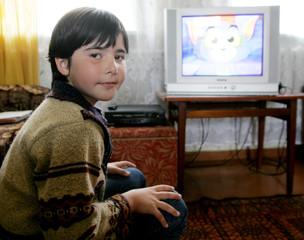 Zalina Amirkhanova watches cartoons at her aunt's home in the town of Beslan.