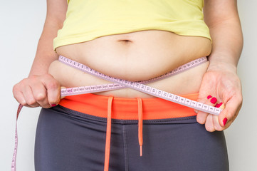 Overweight woman with tape is measuring fat on belly
