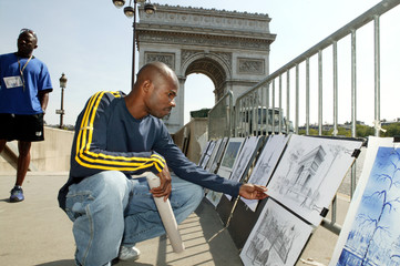 MENS 100 METERS WINNER KIM COLLINS OF ST. KITTS LOOKS AT SKETCHES INCENTRAL PARIS AFTER VICTORY.