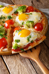 Piece of pizza with eggs, broccoli, tomatoes and parsley close-up. Vertical