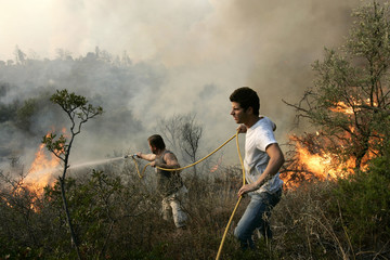 Villagers struggle to battle flames with a small garden hose in the village of Leprio in south Peloponnese