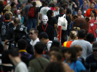 A man with a painted face walks in the crowd along with thousands of attendees at this year's annual Comic Con conference in San Diego