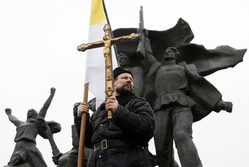 A protester with Orthodox symbols stands next to a monument for revolutionary workers during a demonstration in central Moscow