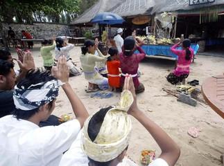 Employees pray in front of their cafe during reopening at Jimbaran in Bali