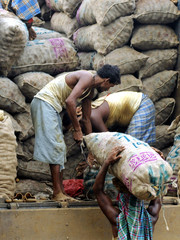 Labourers unload sacks of potatoes from a truck in Agartala