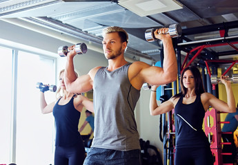 Athletic male and two slim female fitness models doing shoulder exercises with dumbbells.