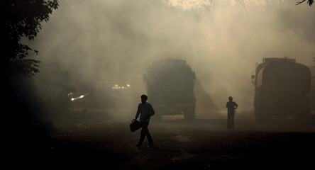 A man walks along a road filled with smoke in an industrial region in Mumbai