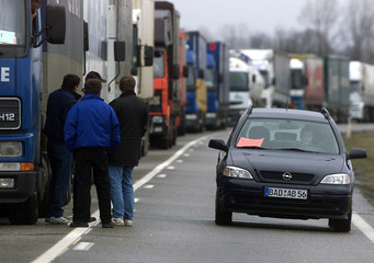 A German-registered car passes through a roadblock manned by striking French truckers on the French-..