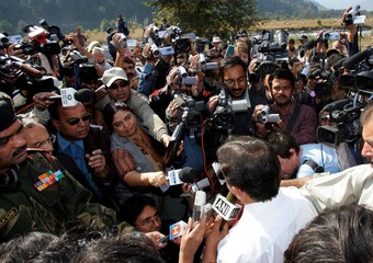 Journalists crowd around Pakistani official after opening of crossing point at LoC in Titrinote in Pakistan-administered Kashmir