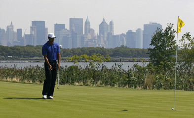 New York's lower Manhattan skyline is seen in the background as Tiger Woods of the U.S. putts on the14th hole