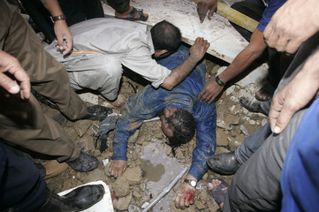 Rescue workers try to recover the trapped body of a fire fighter from a collapsed factory in Karachi