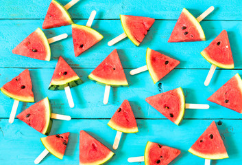 the summer watermelon slice popsicles on a blue rustic wood background