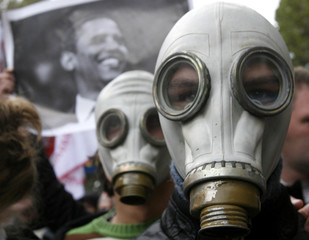 People stand while wearing gas masks as a man holds a portrait of U.S. President-elect Barack Obama in the background during an opposition rally in Tbilisi
