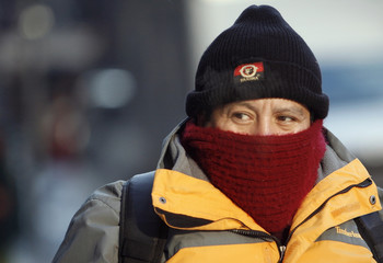A morning commuter covers up against the elements in New York
