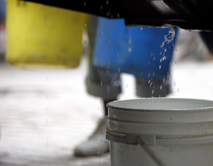 Water dripping from tanker truck into plastic bucket during shortage.