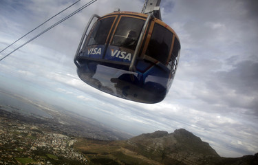 People are reflected in a window as two cable cars meet on their way up and down from Table Mountain