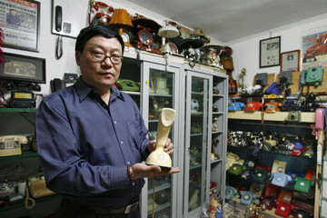 Zhang Dafang poses with one of his telephones from his collection at his apartment in Beijing