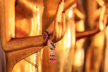 close up on hand about a golden statue in a temple - Bangkok - Thailand