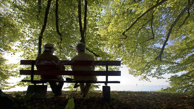 People sit on a bench during a sunny autumn day at Lake Constance in the southern German city of Lindau