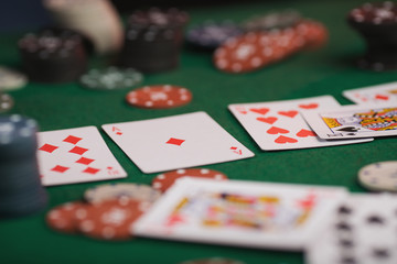 Poker game in men's hands on green table