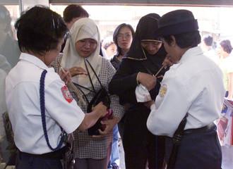 FILIPINO SECURITY WOMEN INSPECT SHOPPERS BAGS IN ZAMBOANGA.
