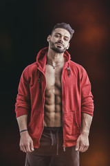 Muscular bodybuilder undressing, removing red hoodie sweater on naked muscle back on dark background