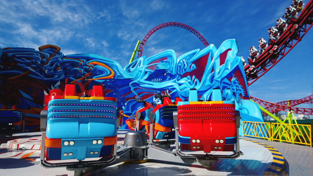 Bright booths on one of the rides in the amusement Park. Roller coaster in the background