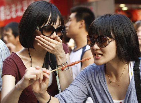 Women try a stick of skewered meat in Beijing