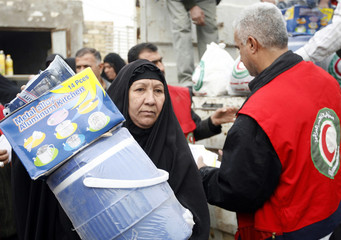 A resident carries a container and kitchen utensils given by the Red Crescent Organization to disabled and poor people in Baghdad's Sadr city