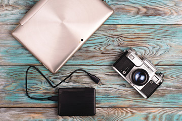 The tablet and camera lying on wooden blue background