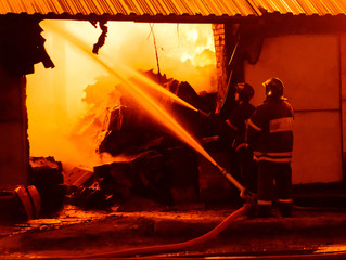 Fototapete - Firefighters extinguish a fire in a burning warehouse
