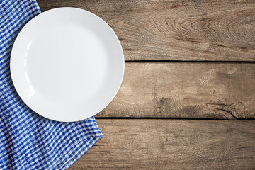 Top view of blank white dish and blue tablecloth on a wood background with copy space.