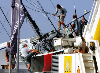 Team members of America's Cup yacht Alinghi of Switzerland inspect damage to the boat lying on its ...
