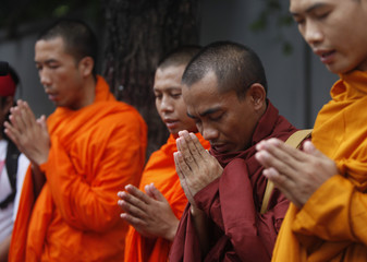 Myanmarese monks, living in Thailand, pray during a rally outside the Myanmar embassy in Bangkok