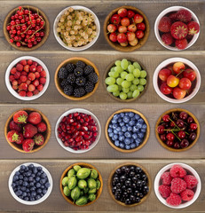 Collage of different fruits and berries on a wooden background. Collection of fruits and berries in a bowl. Top view.