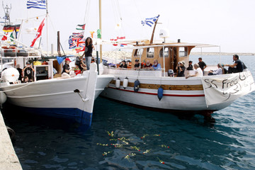 Activists sailing on two boats perform a flower ceremony on sea in Cyprus port of Larnaca