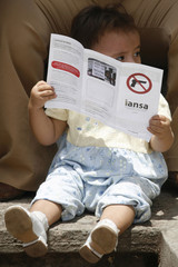 A child holds a leaflet against weapons and violence during an anti-violence march in downtown Tegucigalpa